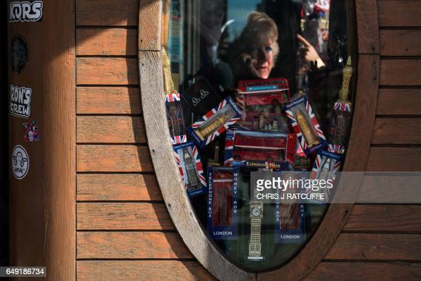 A woman is reflected in the window of a souvenir store in London on March 7 2017 Britain's Finance minister Philip Hammond earlier this week said he...