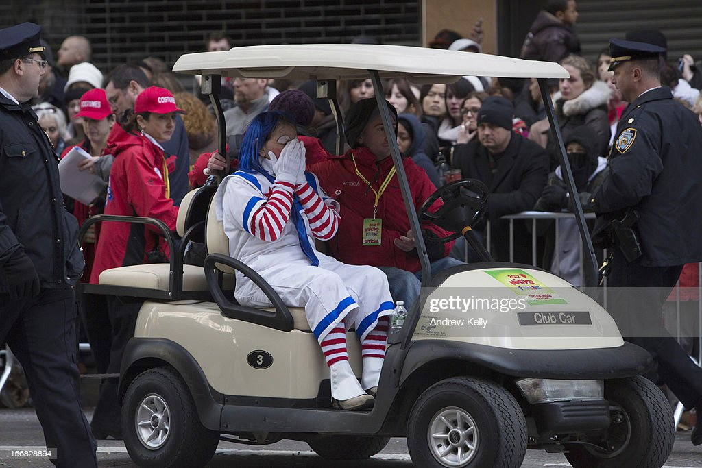 A woman is removed from the scene where a man dressed as a clown collapsed during the 86th Annual Macy's Thanksgiving Day Parade on November 22, 2012 in New York City. Macy's donated tickets and transportation to this year's Thanksgiving Day Parade to 5,000 people from neighborhoods hardest hit by Superstorm Sandy.