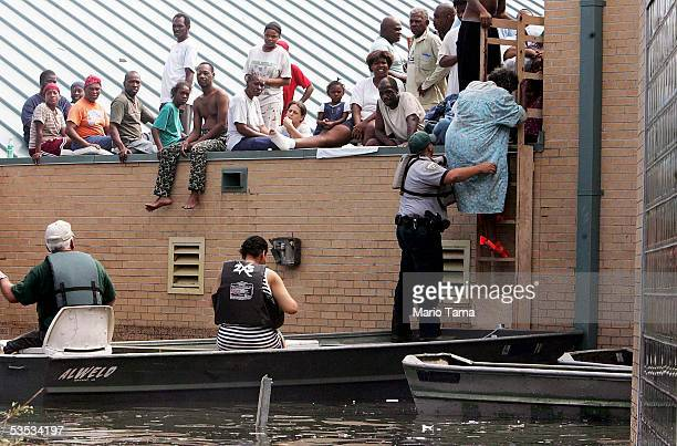 A woman is rescued from a school rooftop after being trapped with dozens of others in high water in Orleans parish during the aftermath of Hurricane...
