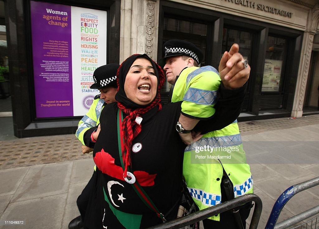 A woman is restrained by police officers as she taunts proMuammar Gaddafi demonstrators near the Libya Conference being held at Lancaster House on...