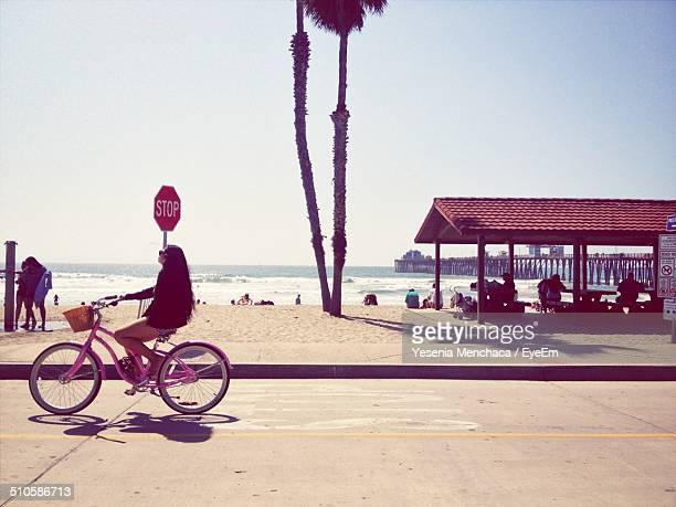 Woman is riding bicycle by the shore