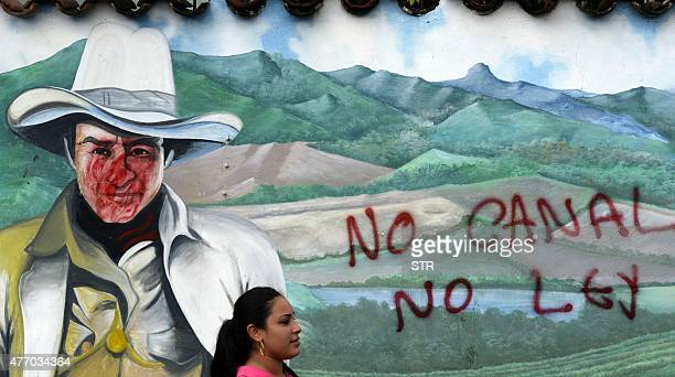 A woman is seen in front of a wall with a graffiti reading 'No canal no law' during a protest against the construction of an interoceanic canal in...