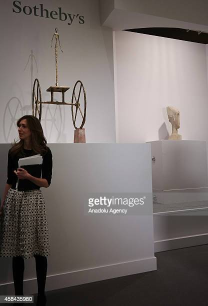A woman is seen in front of the Alberto Giacometti's Chariot which was sold for $101 million during an auction at Sotheby's in New York United States...