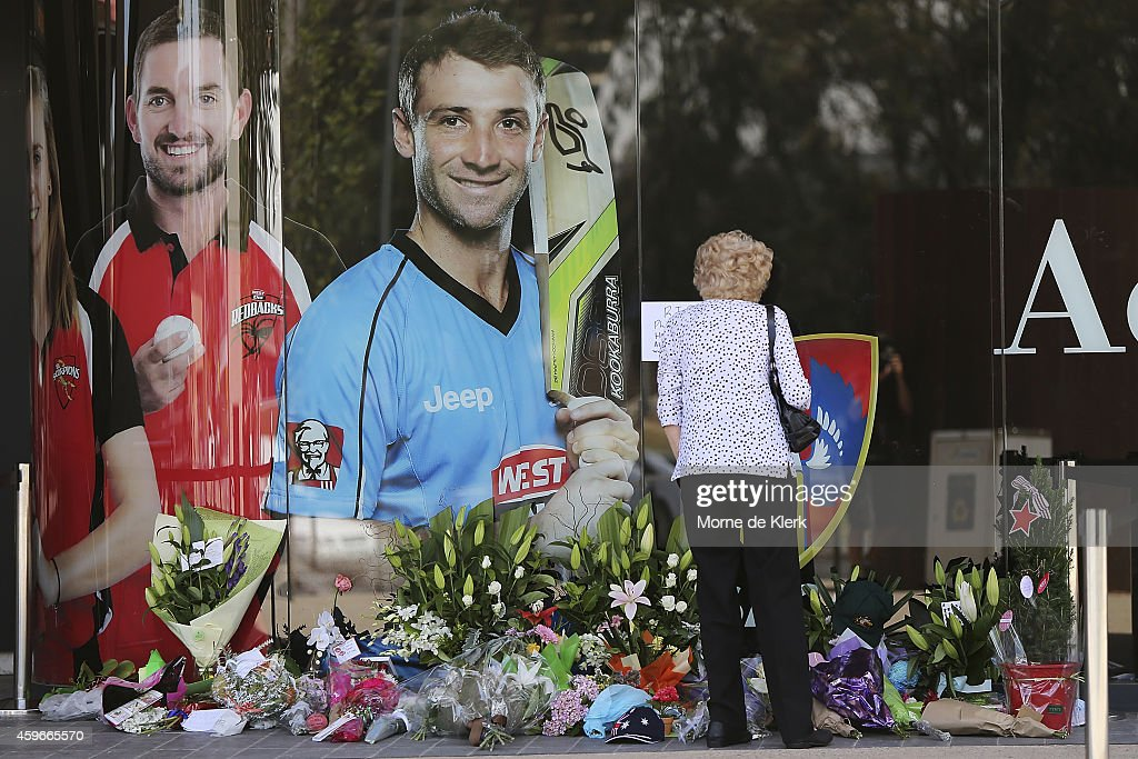 A woman is seen lying flowers amongst other tributes next to a photograph of Phil Hughes outside the Adelaide Oval on November 28, 2014 in Adelaide, Australia. Cricket player, Phil Hughes passed away aged 25, as a result of head injuries sustained during the Sheffield Shield match between South Australia and New South Wales at the SCG on Tuesday.