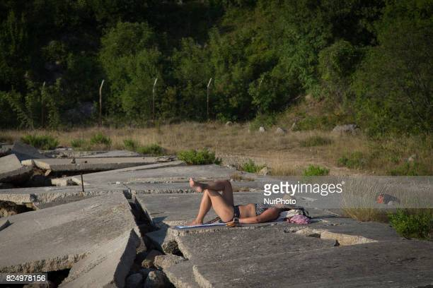 A woman is seen sunbathing on the island of Krk near a disused petro chemical plant on 23 July 2017