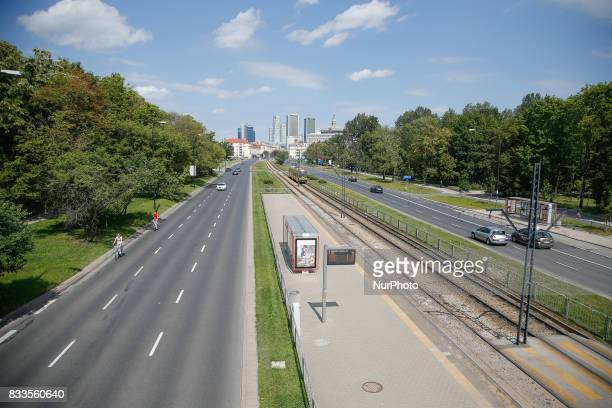 A woman is seen taking a photo with her phone of the Warsaw skyline from the Pole Mokotowskie park bridge on 5 August 2017
