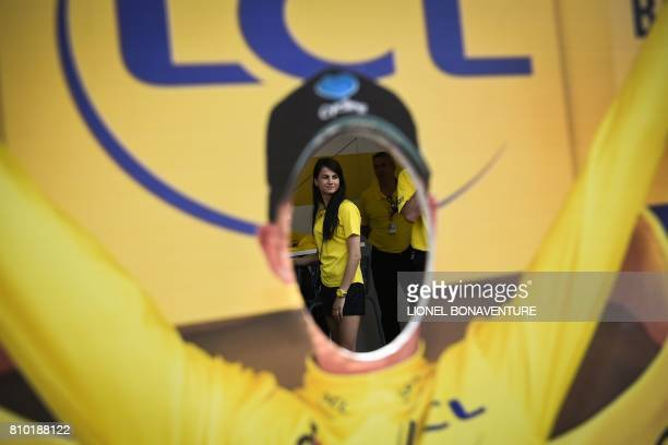 A woman is seen through shows a lifesized silhouette of the overall leader's yellow jersey with a hole for the head to be photographed through at the...