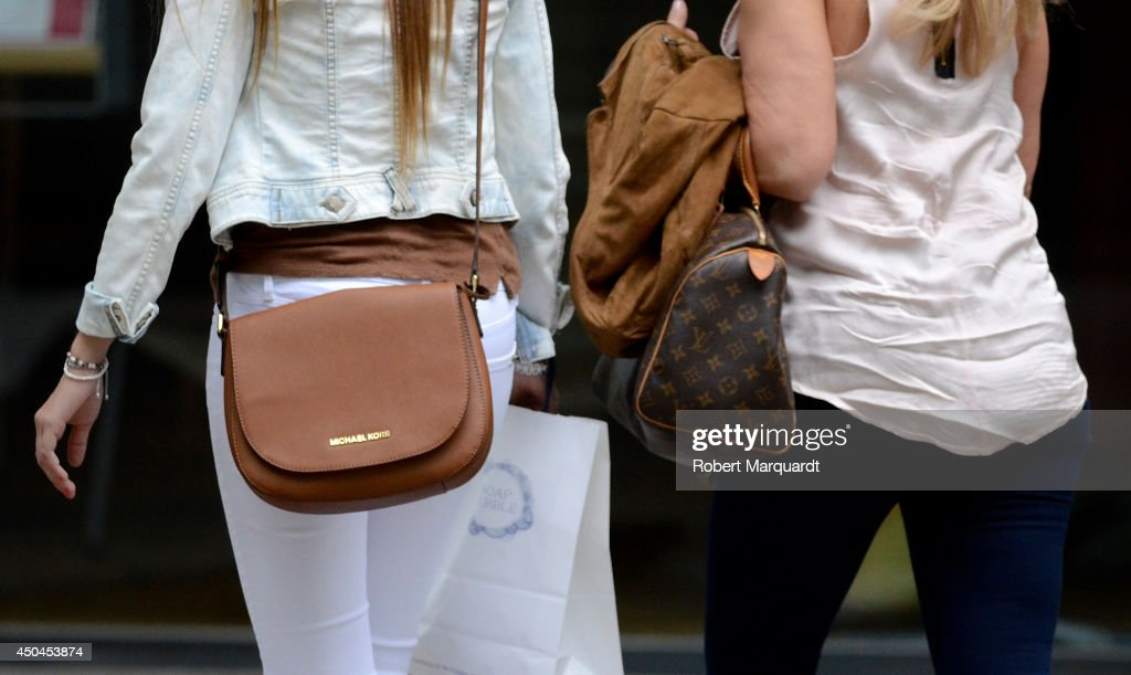 A woman (L) is seen wearing a Michael Kors handbag on June 11, 2014 in Barcelona, Spain.