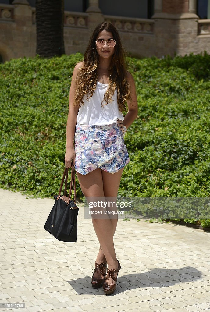 A woman is seen wearing a shirt by Urban Outfitters, skirt by Mustard Seed, shoes by Louboutin, a handbag by Longchamp and Rayban sunglasses during the 080 Barcelona Fashion Week on July 3, 2014 in Barcelona, Spain.