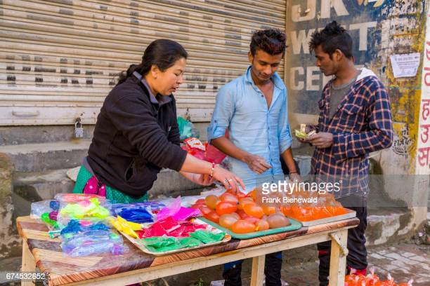 A woman is selling color powder and water bombs for the Holi Festival