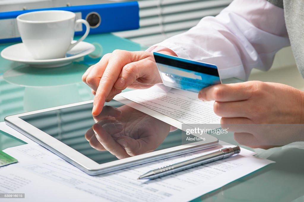 Mulher é fazer compras online com tablet pc : Foto de stock