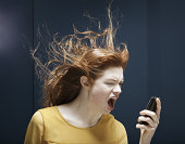woman is shouting into phone.
