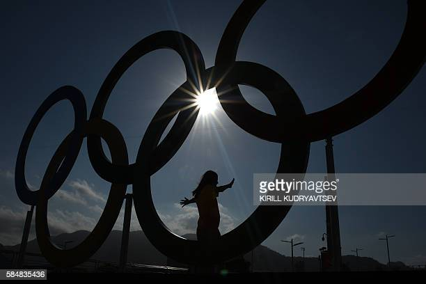 TOPSHOT A woman is silhouetted as she poses with the Olympic rings at the Olympic park on July 31 2016 in Rio de Janeiro ahead of the 2016 Rio...