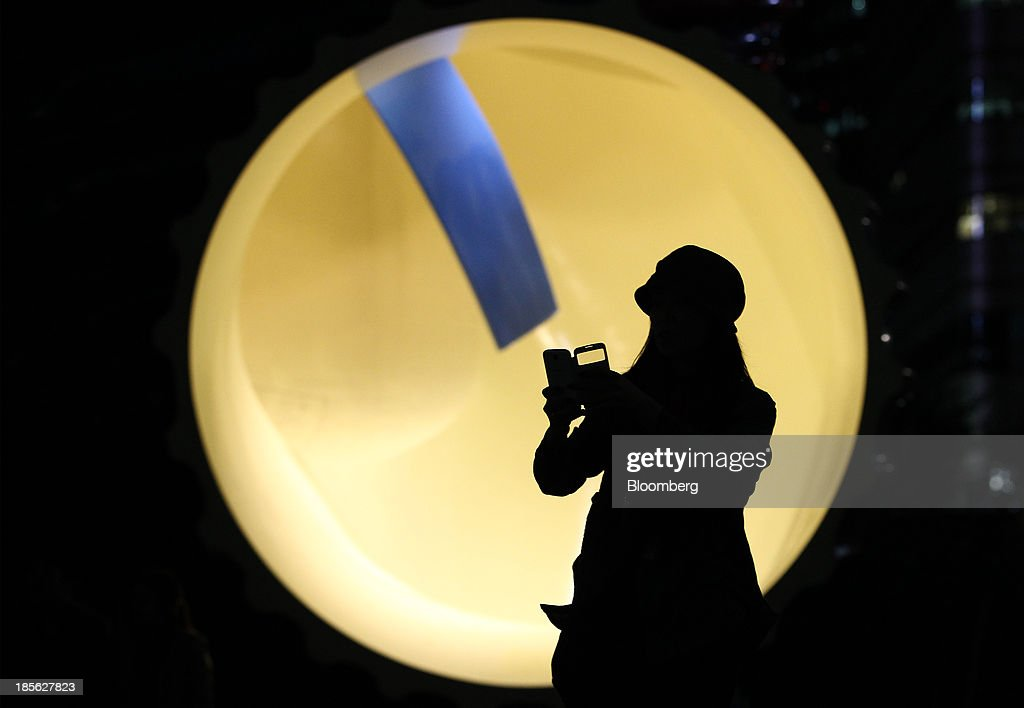 A woman is silhouetted as she takes a photograph using her mobile device in front of the sculpture at Cheonggye Stream in Seoul, South Korea, on Tuesday, Oct. 22, 2013. Samsung Electronics Co. is scheduled to release third-quarter earnings on Oct. 25. Photographer: SeongJoon Cho/Bloomberg via Getty Images