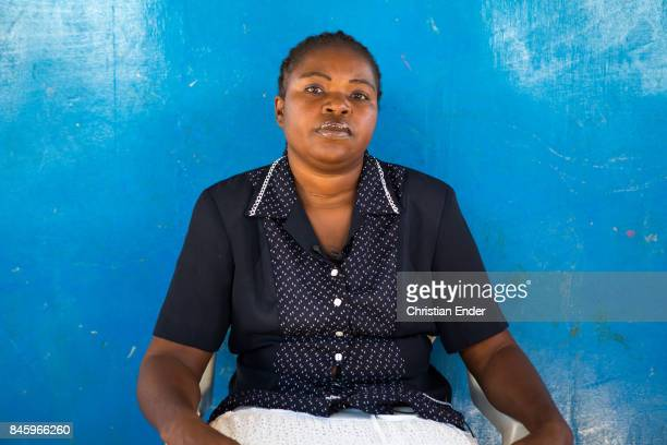 PortauPrince Haiti December 09 2012 A woman is sitting in front of a blue wall in the refugee camp Parc Colofe in PortauPrince The camp exist since...