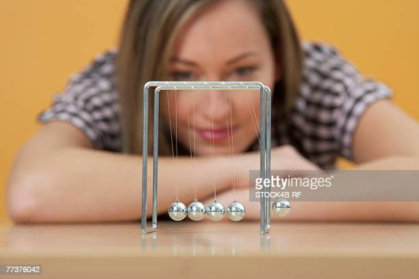 A woman is sitting in front of a shot-put pendulum