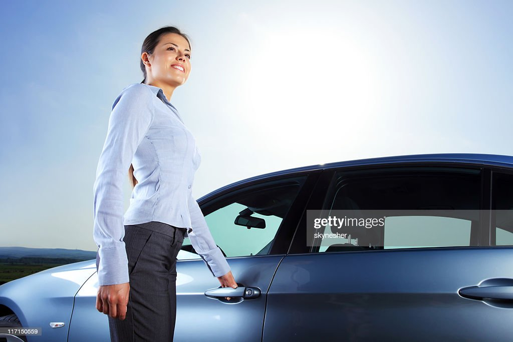 Woman is smiling. She entering in a car : Stock Photo
