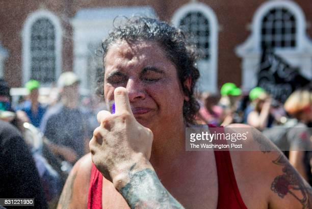 A woman is sprayed with water to clean her face of pepper spray during a Unite the Right rally on Aug 12 2017 in Charlottesville Virginia