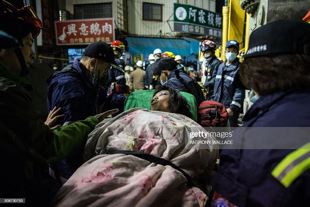A woman is taken to an ambulance by rescue workers after being extracted by a crane from the rubble of a collapsed building in the southern Taiwanese city of Tainan following a strong 6.4-magnitude earthquake that struck early on February 6, 2016. A powerful earthquake in Taiwan felled a 16-storey apartment complex full of families who had gathered for Lunar New Year celebrations February 6, with at least eleven dead and more than 30 feared trapped. AFP PHOTO / ANTHONY WALLACE / AFP / ANTHONY WALLACE