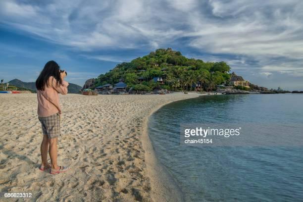 A woman is taking photo of a beautiful beach and island at Nang Yuan Island, Thailand.