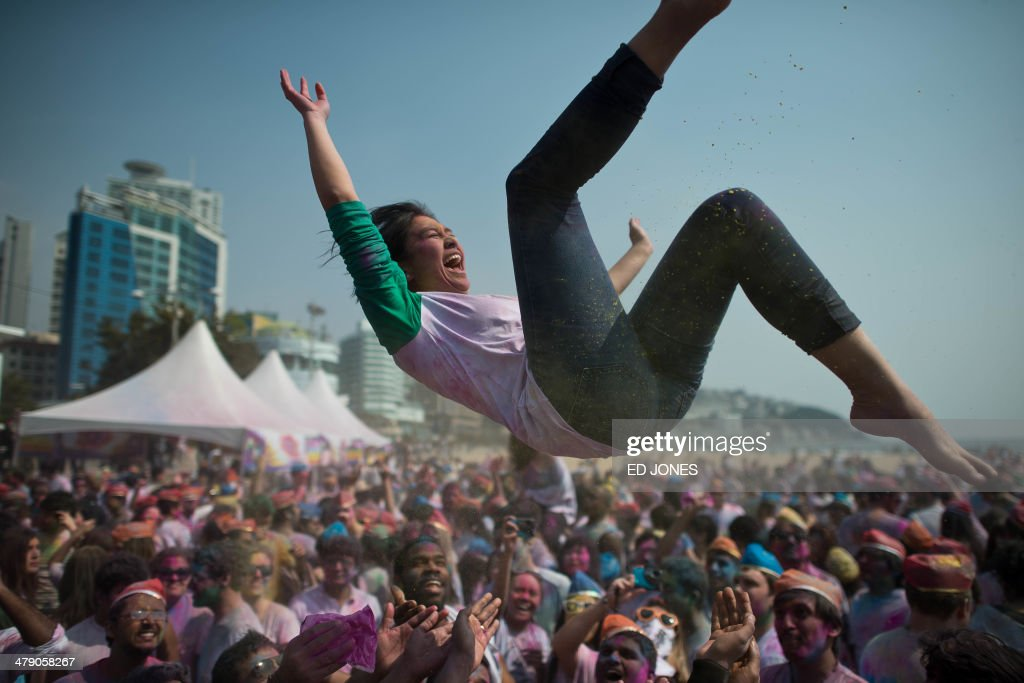 A woman is thrown in the air as revellers take part in Holi celebrations organised by members of South Korea's Indian community at Haeundae beach in the southeastern city of Busan on March 16, 2014. Holi, the popular Hindu spring festival of colours, is observed in India at the end of the winter season on the last full moon of the lunar month. AFP PHOTO / Ed Jones