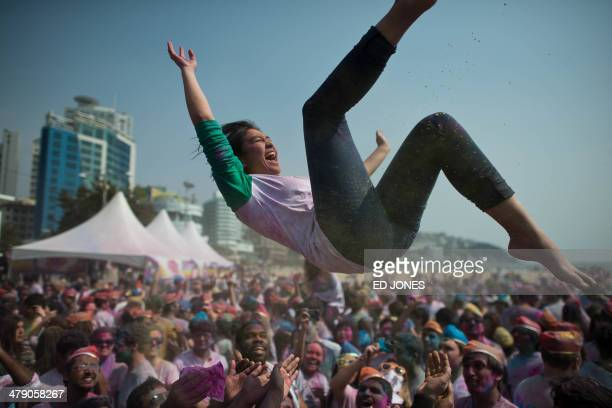 A woman is thrown in the air as revellers take part in Holi celebrations organised by members of South Korea's Indian community at Haeundae beach in...