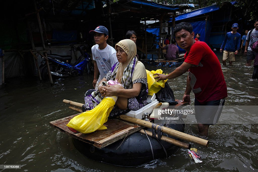 A woman is transported over a flooded road on a make-shift raft as major floods hit North Jakarta o on January 20, 2013 in Jakarta, Indonesia. The death toll has risen to at least 21 since severe flooding struck the city on January 17. The US has offrered US$150,000 (Rp 1.44 billion) in aid.