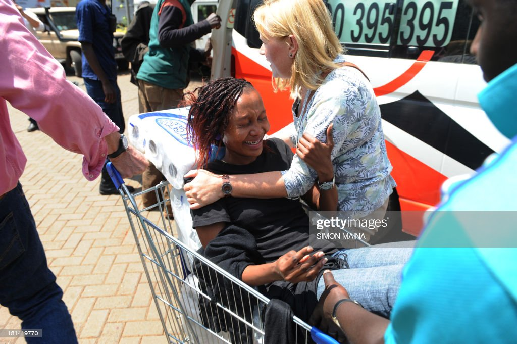 A woman is trolled into an ambulance after masked gunmen stormed an upmarket mall and sprayed gunfire on shoppers and staff, killing at least thirteen on September 21, 2013 in Nairobi. The Gunmen have taken at least seven hostages, police and security guards told an AFP reporter at the scene. AFP PHOTO/SIMON MAINA