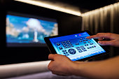Woman is using tablet for remote control of home cinema theater