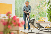 Woman is vacuuming beige carpet next to a designer table in big living room