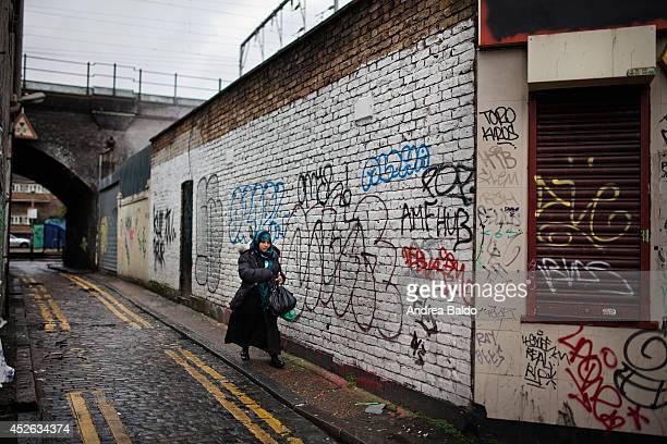 A woman is walking in an alley in Bethnal Green East London