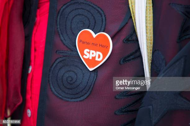 A woman is wearing a heart shaped pin during an election campaign rally of Martin Schulz chancellor candidate of the German Social Democrats August...
