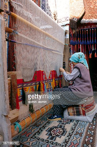 Woman is weaving traditional Turkish carpet in her house