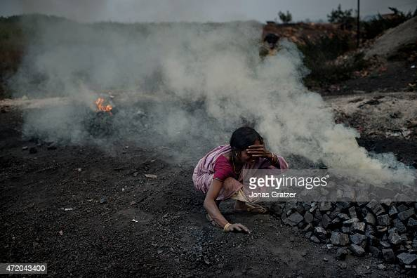A woman is working in the cloud of toxic smoke that comes out of the ground methane and other toxic gases spew out from the open wounds in the...