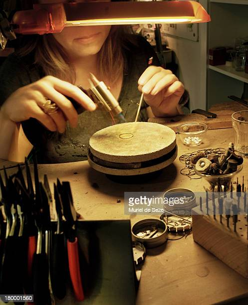 Woman jeweller welding golden ring
