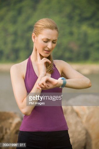 Woman jogger checking pulse : Stock Photo