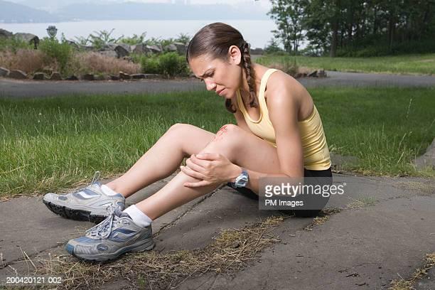 Woman jogger holding injured knee