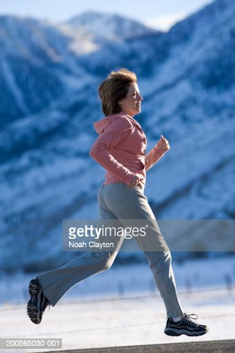 Woman jogging against backdrop of mountains : Stock Photo
