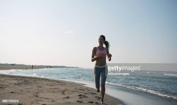 Woman jogging at beach.