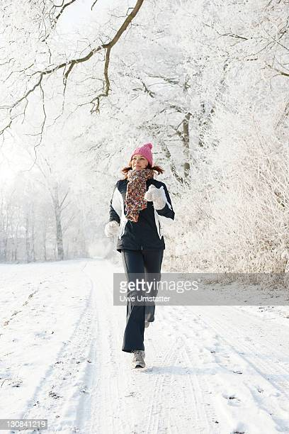 Woman jogging in a wintery landscape