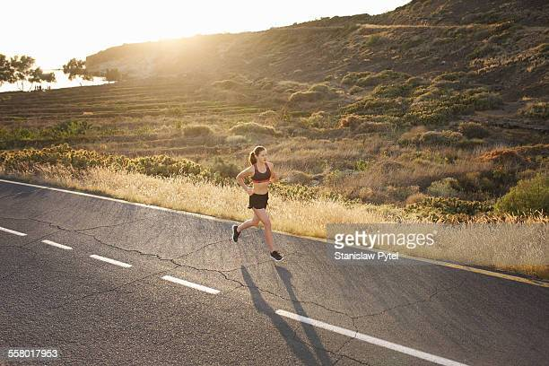 Woman jogging in wild road at sunset