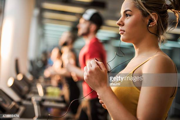 Woman jogging on a running track in a health club.