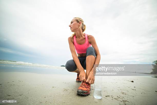 Woman jogging on beach tying shoes