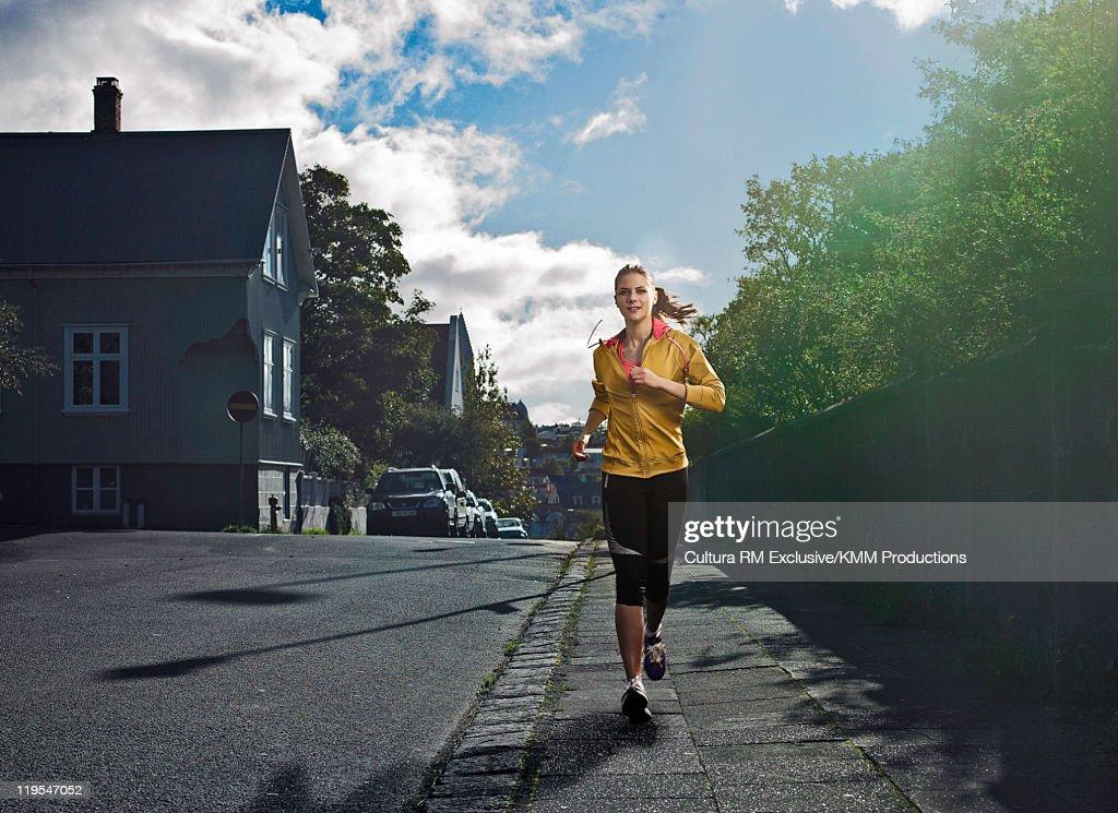 Woman jogging on city street : Stock Photo
