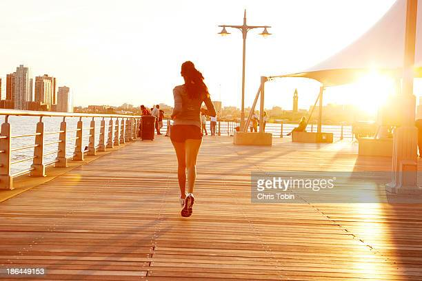 Woman jogging on pier at sunset