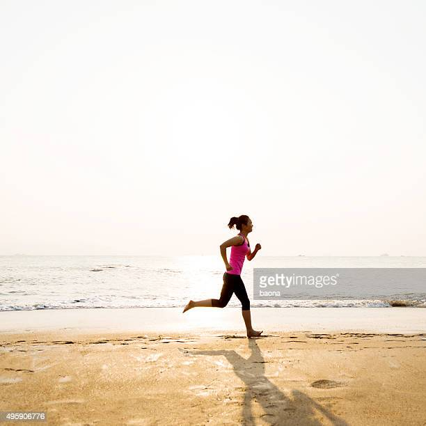 Woman jogging on shore at sunrise