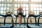 Horizontal shot of woman jogging on treadmill at health club. Female working out at a gym running on a treadmill.