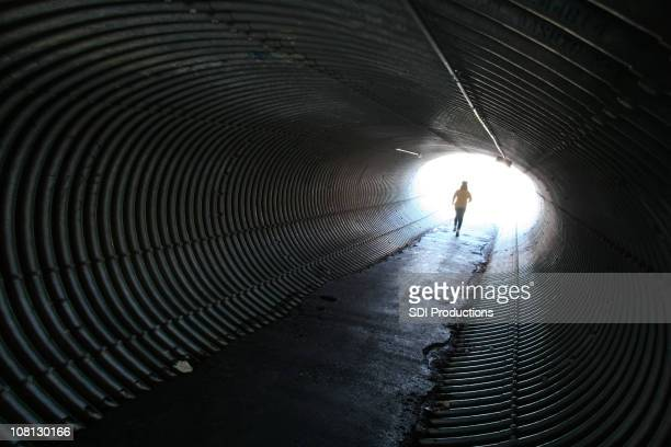 女性のジョギングを丸型金属トンネル