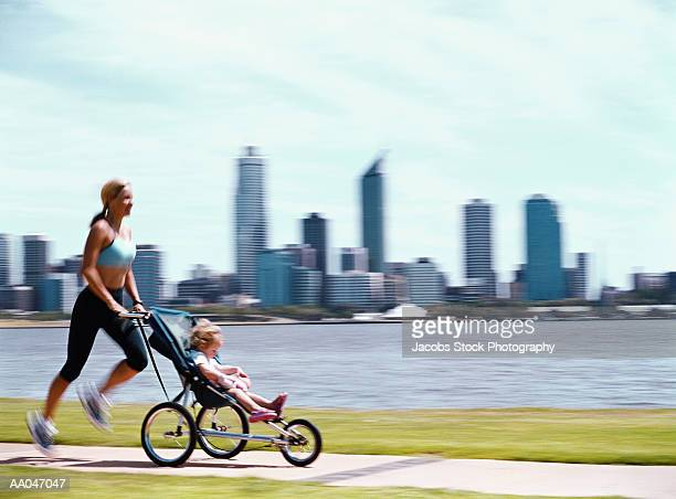 Woman jogging with daughter (2-4) in baby jogger (blurred motion)