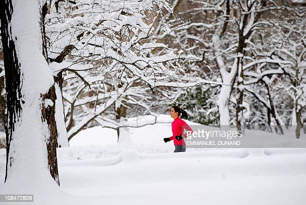 A woman jogs after heavy snow falls in Central Park in New York January 27 2011 New York shut down two airports public schools and most city services...